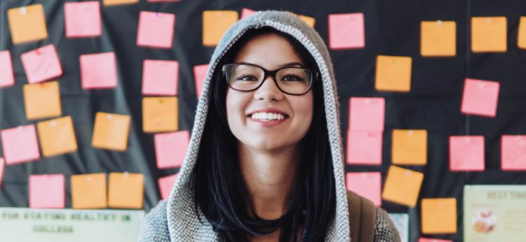 girl smiling and wearing glasses and a hoodie