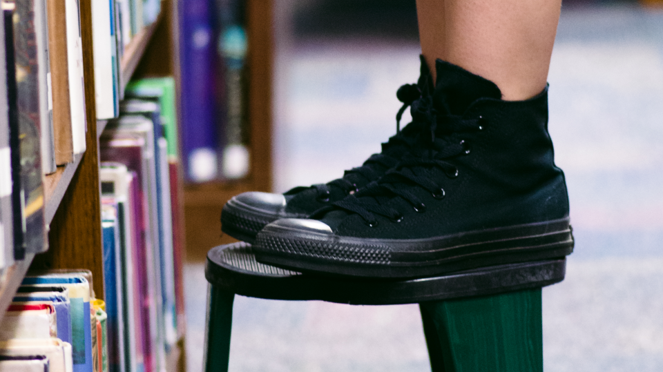 black high-top sneakers on a stool
