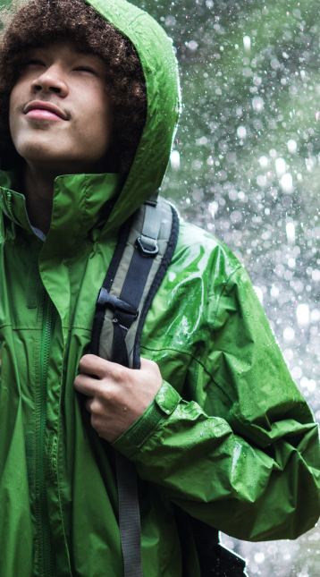 boy wearing green raincoat in rain
